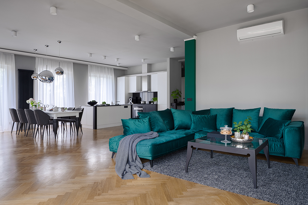 Spacious apartment with beautiful kitchen with dining table and elegant living room with stylish green corner sofa and modern coffee table